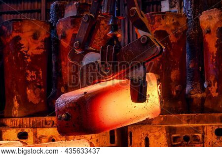 The Red-hot Metal Casting Is Transported By A Metallurgical Crane.