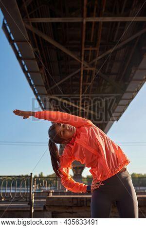 Vertical Narrow Shot Of Millennial Gen Z Girl In Sportswear Headphones Stretch Workout Alone Outdoor