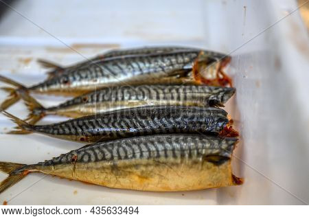 Lots Of Smoked Mackerel Carcasses. The Fish Lies In A Heap In A White Plastic Box. Delicious And Nut