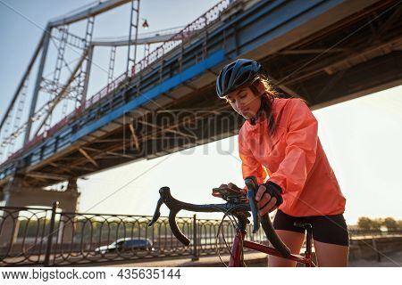 Millennial Sporty Fit Sportswoman On Bike Browse Smartphone Cycle Bike Outdoors. Young 20s Active Fi