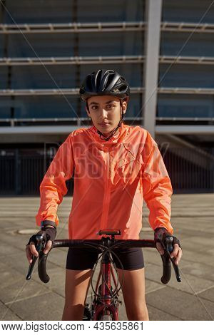 Vertical Narrow Image Portrait Of Motivated Millennial Active Female Cyclist In Sportswear Helmet Cy