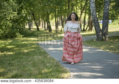Middle-aged Attractive Woman With Dark Hair, Enjoying Nature In The Forest. Walking Among The Trees