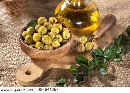Bottle With Olive Oil And Olives In A Wooden Bowl