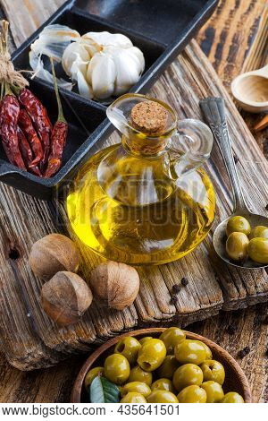 Olive Oil And Olives On Textured Board
