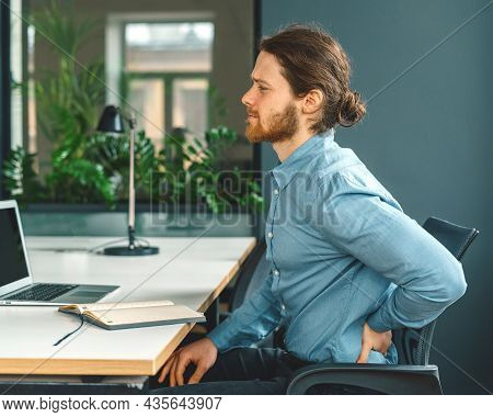 Painful Feeling. Side View Of Tired Man Office Worker Suffering From Terrible Pain In Lower Back Or
