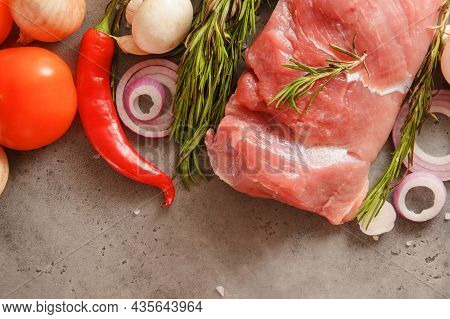 Pork Tenderloin With Rosemary, Mushrooms, Tomato,  Onion, Chili Pepper  On A Gray