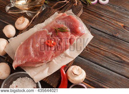 Pork Tenderloin With Mushrooms,  Salt , Chili Pepper, Rosemary On A Dark Wooden Background
