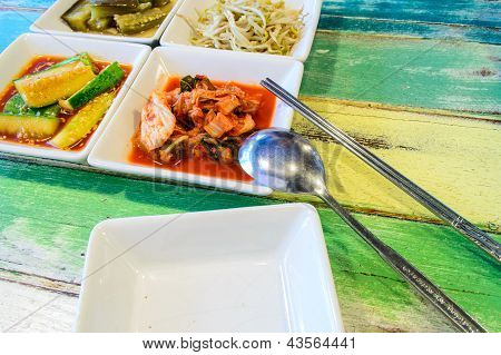 Korean Cuisine, Kimchi On White Square Dish With Spoon And Chopsticks.