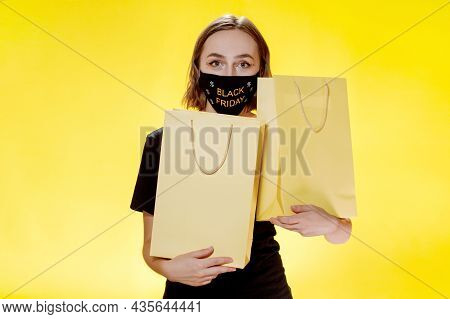 Joyful Woman With Packages On Yellow Background, Shopping Trip. Studio Portrait. Black Friday Sale