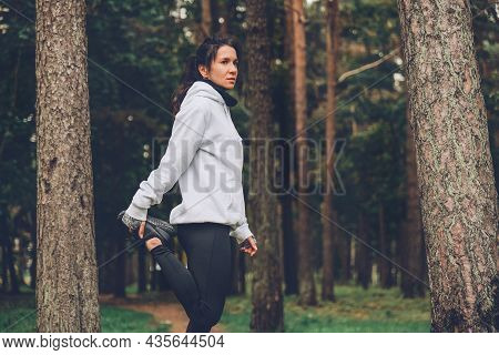 Woman Stretching In Autumn Forest. Exercising Outdoors