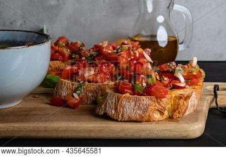 Italian Tomato Bruschetta On A Wooden Board And A Bowl With Diced Tomatoes, And Basil With Garlic
