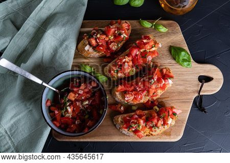 Italian Tomato Bruschetta On A Wooden Board And A Bowl With Diced Tomatoes, And Basil With Garlic, T