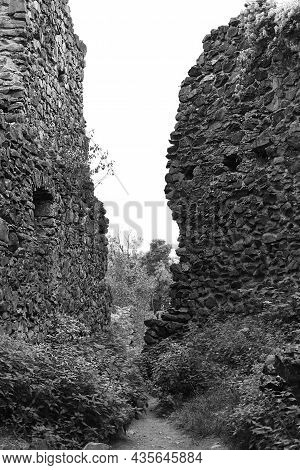 The Passage Between The Old Stone Walls Of An Abandoned Mystical Medieval Castle. Halloween Mystery