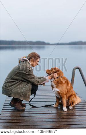 Young Caucasian Woman Caress Brown Nova Scotia Duck Tolling Retriever. Girl Travelling With Dog. Fri