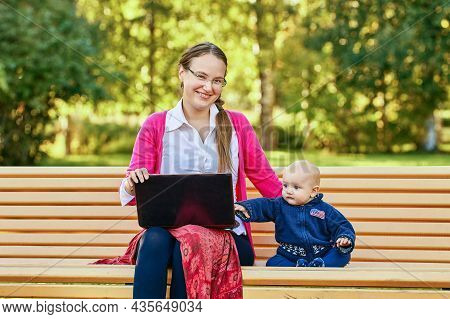 Mother With Baby Makes Teleworking With Laptop Outdoors.