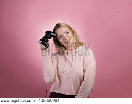 A Gamer Who Is Passionate About The Process. A Cute Blonde Is Holding A Gamepad In Her Hands, Lookin