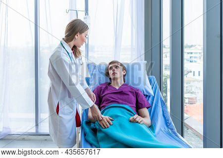 Female Doctor Hold The Leg To Heal The Illness To A Man Patient On Bed With Symptom In Hospital Back