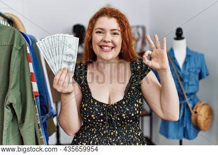 Young redhead woman holding shopping bags and dollars doing ok sign with fingers, smiling friendly gesturing excellent symbol
