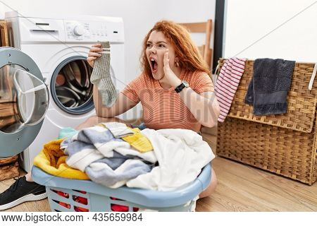Young redhead woman putting dirty laundry into washing machine shouting and screaming loud to side with hand on mouth. communication concept.