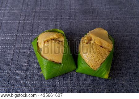 Sticky Rice With Custard Wrapped In Banana Leaves Is Thai Dessert On A Wooden Table