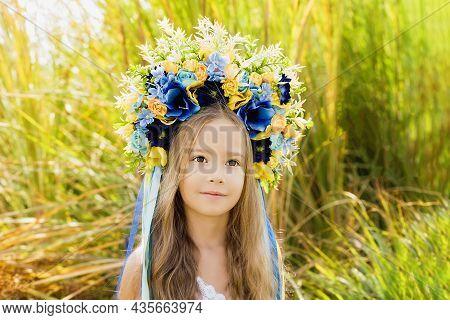 Girl In Traditional Ukrainian Wreath On Head Blue And Yellow Flag Of Ukraine In Field. Ukraine's Ind