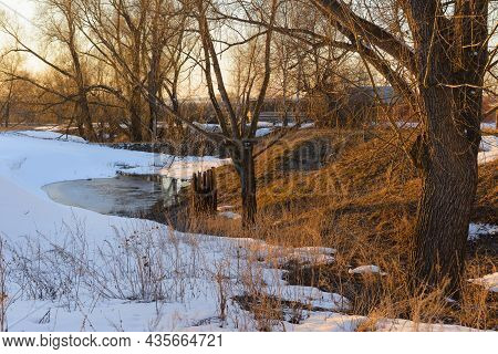 Spring Evening Landscape With Melting Snow In A Ravine With Trees