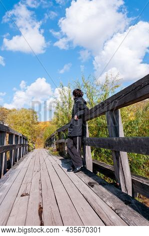 A Girl In Black Clothes Stands With Her Back On A Wooden Bridge On An Autumn Sunny Day