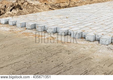 Pavement Repairs And Paving Slabs Laying On The Prepared Surface, With Tile Cubes In The Background.