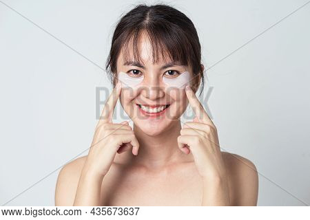 Asian Woman Smiling And Pointing Show Patches Mask Under Eyes For Anti Wrinkles And Eye Dark Circles