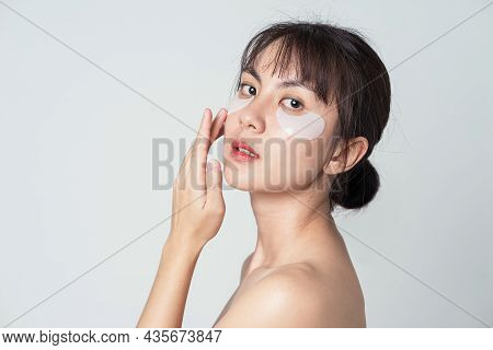 Portrait Posing Asian Woman Applying Patches Mask Under Eyes For Anti Wrinkles And Eye Dark Circles