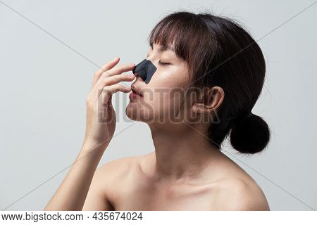 Asian Woman Applying Mask Charcoal Deep Cleansing Nose Pore Strip On Fresh Clean Skin. Beauty And Sk
