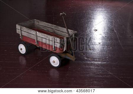 Vintage Rusted Red Metal Utility Wagon On Old Wood Floor