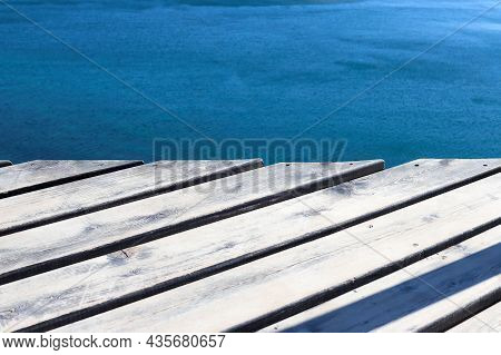 Wooden Platform Over Sea Water. Old Wood Boards Texture Background And Surface Of Sea Or Ocean. Pede