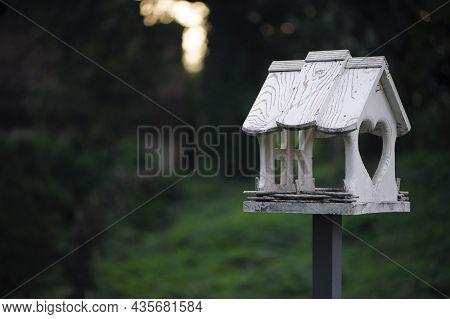 Bird Feeder In The Autumn Park. A Closeup Photo Of A White Wooden Birdhouse In The Park. Bird Feeder