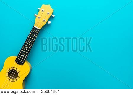 Top View Of Ukulele With Copy Space. Yellow Colored Wooden Ukulele Guitar On The Turquoise Blue Back