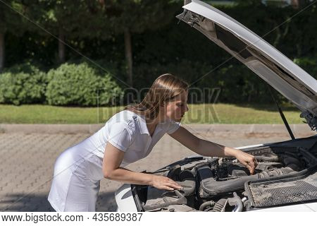 Car Breakdown. The Woman Lifted The Hood Of The Car, Bent Over The Engine And Is Trying To Independe