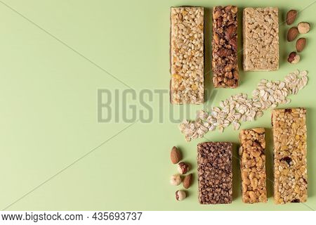 Protein Bars Assortment With Ingredients On Color Background. Healthy Granola Bars. Place For Text,