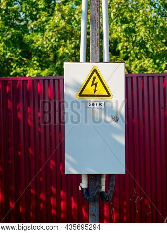 Close-up Of A Gray Metal Electric Shield Hanging On A Pole. A Warning Sign. Red Fence In The Backgro