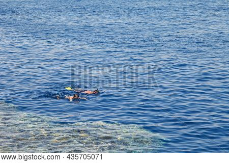 Two Young Athletes With Fins, Mask And Snorkel In The Sea.