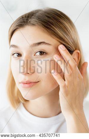 Cream Moisturizing. Skin Care. Beauty Cosmetology. Fresh Young Woman Applying Under Eye Product On F