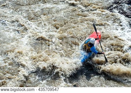 A Man In A Kayak Floats On A Mountain River In The Spray From The Rapids. Dark Muddy Water And Rapid