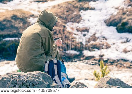 The Traveler Sits On A Stone And Drinks Tea From A Metal Cup. Rest After The Hike. Rest In The Highl