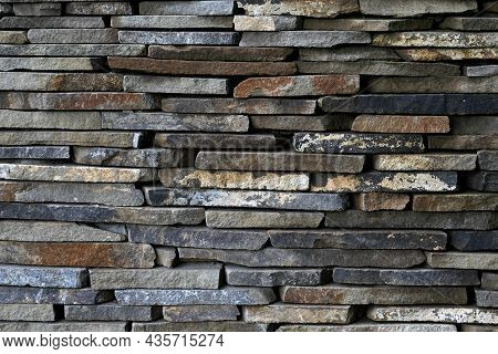 Dark Brown Rough Stone Wall. Brick Wall Stack Background. Rock Wall Surface. Stony Texture. Abstract