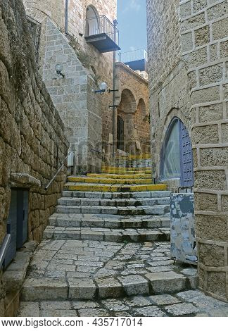 An Old Narrow Street In Old Jaffa Paved With Paving Stones With Houses With Walls Of Large Stones An