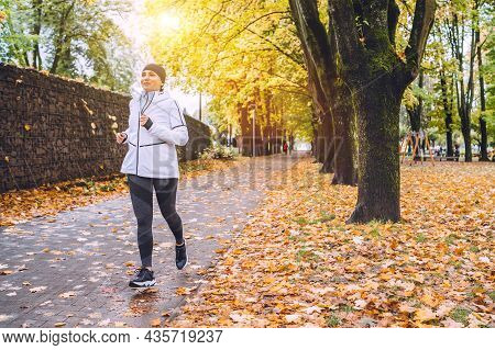 Sincerely Smiling Athletic Woman Have A Jogging In The Autumnal City Park. Young Fitness Female Smil