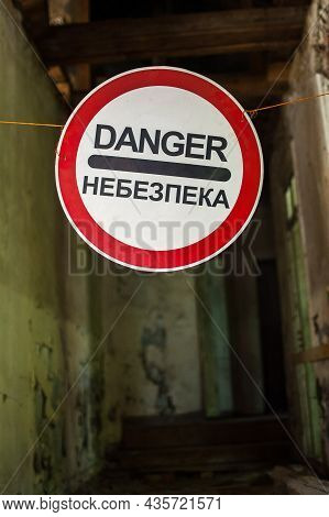 Old Wrecked House With Danger In English And In Ukrainian Warning Sign, Abandoned Building, Uninhabi