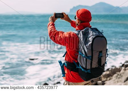 A Traveler Takes Pictures Of Nature On A Smartphone. A Traveler With A Backpack Travels Through Pict
