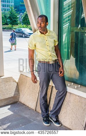 Dressing In A Light Yellow Shirt, Gray Pants And Black Shoes,  A Young Black Guy Is Standing By A Gl