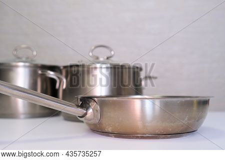 Stainless Steel Pot, Stockpot And Frying Pan On White Table, Eco Friendly Kitchen Utensils Without H