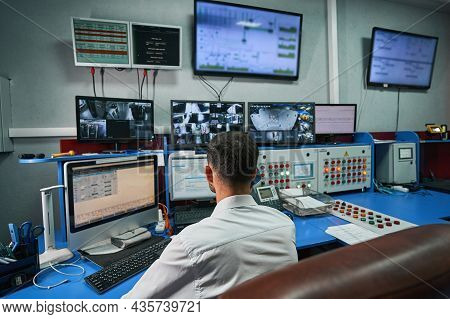 Server Administrator Looking After Data Center Rooms Through Monitors